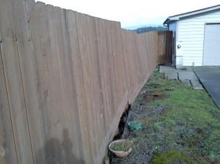 Fence and earth sliding down hill